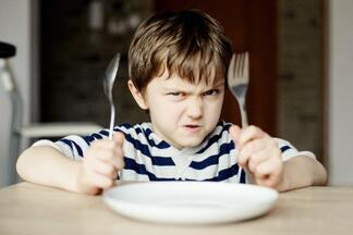 Hungry boy with empty plate